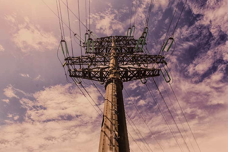 Transmission tower (power tower, electricity pylon, steel lattice tower) at twilight in US. Texture high voltage pillar, overhead power line, industrial background. Copy space