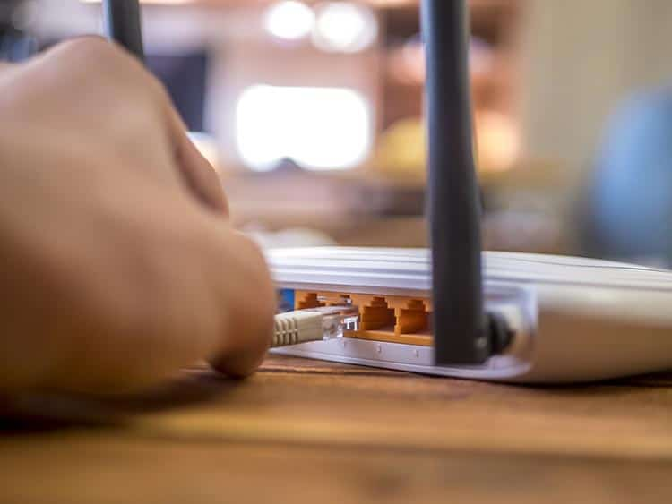 close up hand inserting ethernet wire in wi-fi router on wooden table